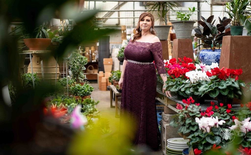Bride poses in a greenhouse. She wears a long, purple lace dress with a silver belt around her waist.