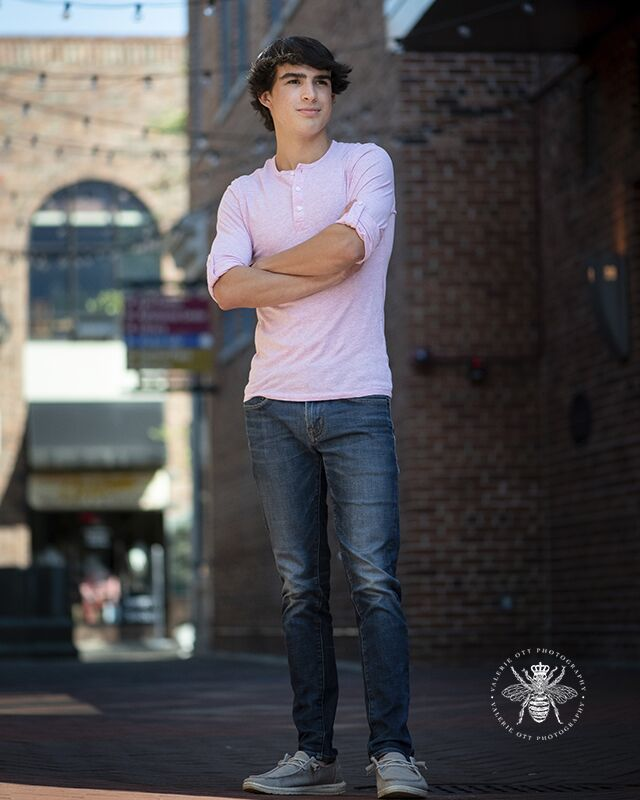 Portage Northern senior guy poses standing with his arms crossed. He wears jeans and a pink shirt.
