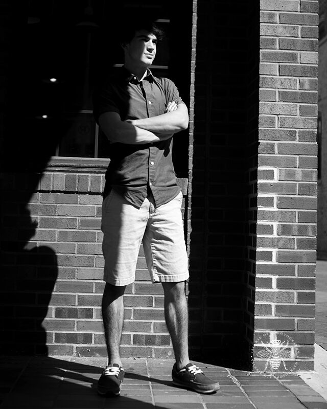 Portage Northern senior guy poses standing with his arms crossed in the shadows in front of a brick wall. The image is in black and white.