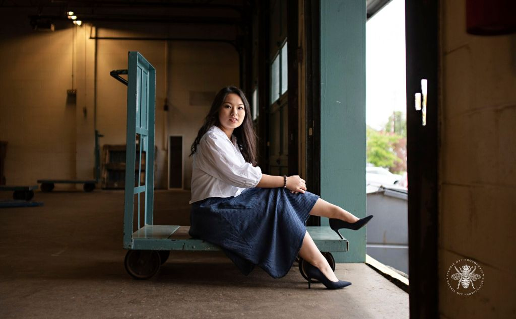 Portage Central senior girl poses sitting on a loading dock. She wears a white button down top with puffed sleeves, black high heels, and a long blue skirt.