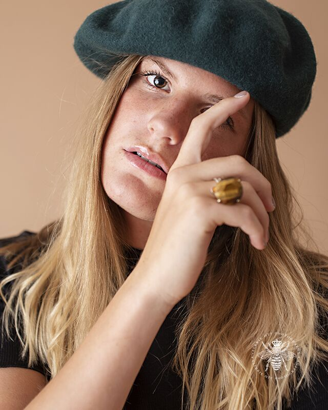 Girl poses with her hand touching her face in a studio. She wears a ring and a dark green beret.