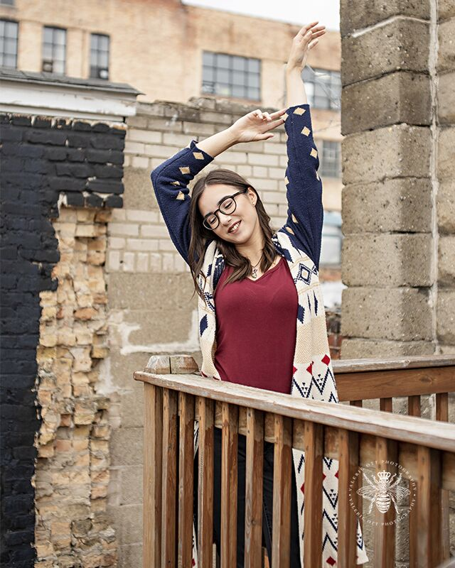 Loy Norrix senior girl poses with her hands above her head on a balcony. She wears glasses and a patterned cardigan.