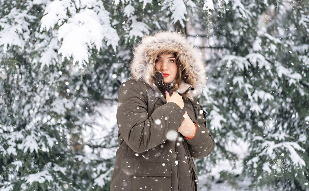 Senior girl poses in front of snow covered pine trees with snow falling around her. She wears a coat with a fur lined hood and red lipstick.