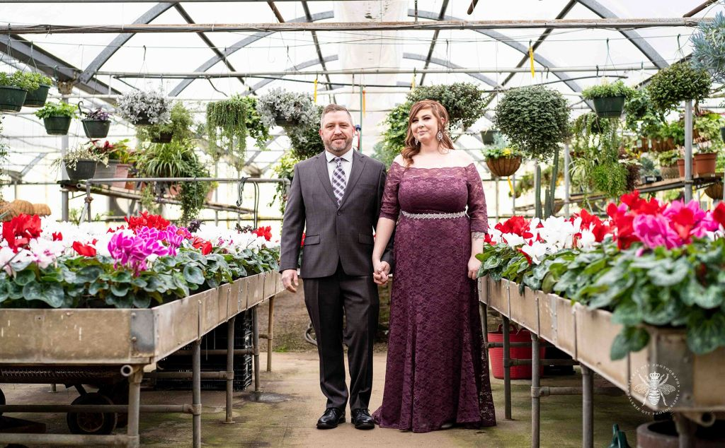 Couple poses holding hands in a greenhouse. The bride wears a long, purple lace dress with a silver belt around her waist. The groom wears a suit and patterned tie.