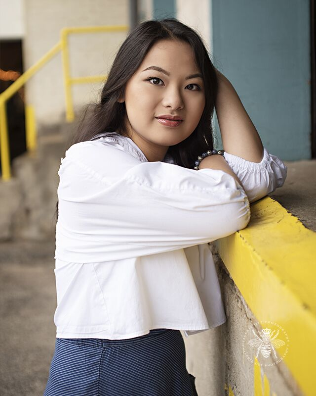 Portage Central high school girl poses leaning on a loading dock. She wears a white button down top with puffed sleeves.