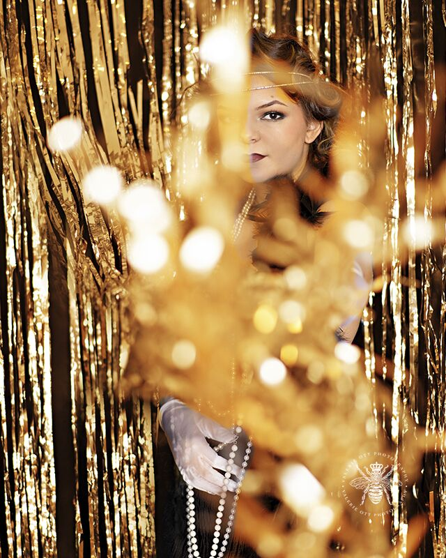 Mattawan senior poses for styled session in West Michigan. She wears her hair in pin curls, red lipstick, white gloves, pearl necklaces, a feather boa, and a flapper dress. She standsl in front of a shimmering gold backdrop.