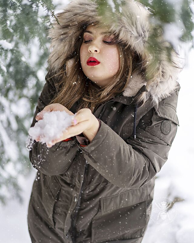 Girl poses in front of snow covered pine trees with snow falling around her. She blows on a pile of snow in her hands and wears a coat with a fur lined hood and red lipstick.