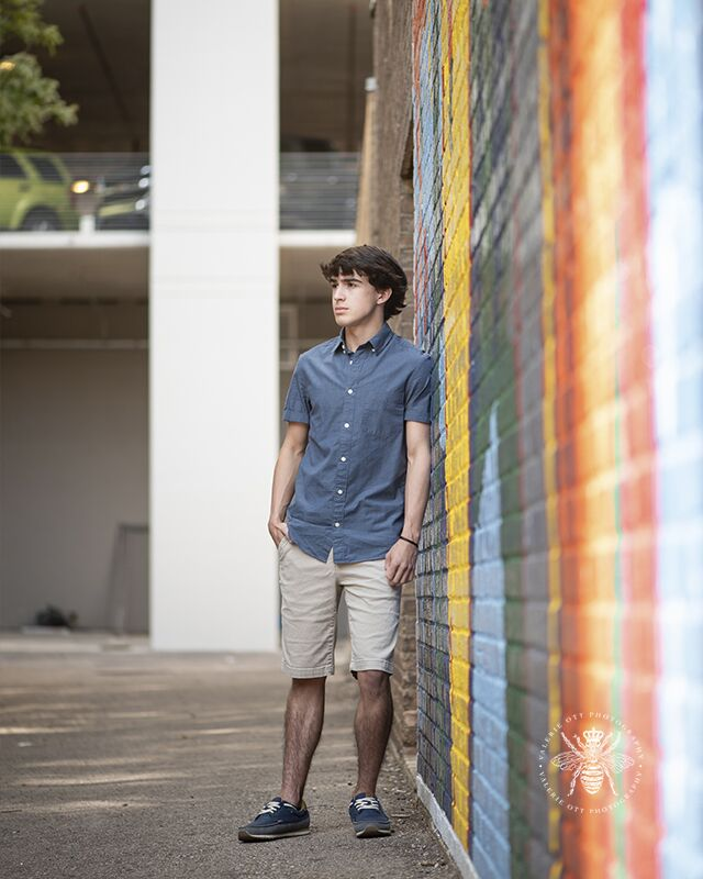 Portage Northern senior guy poses leaning against a mural in Downtown Kalamazoo. He wears khaki shorts and a blue button down top.