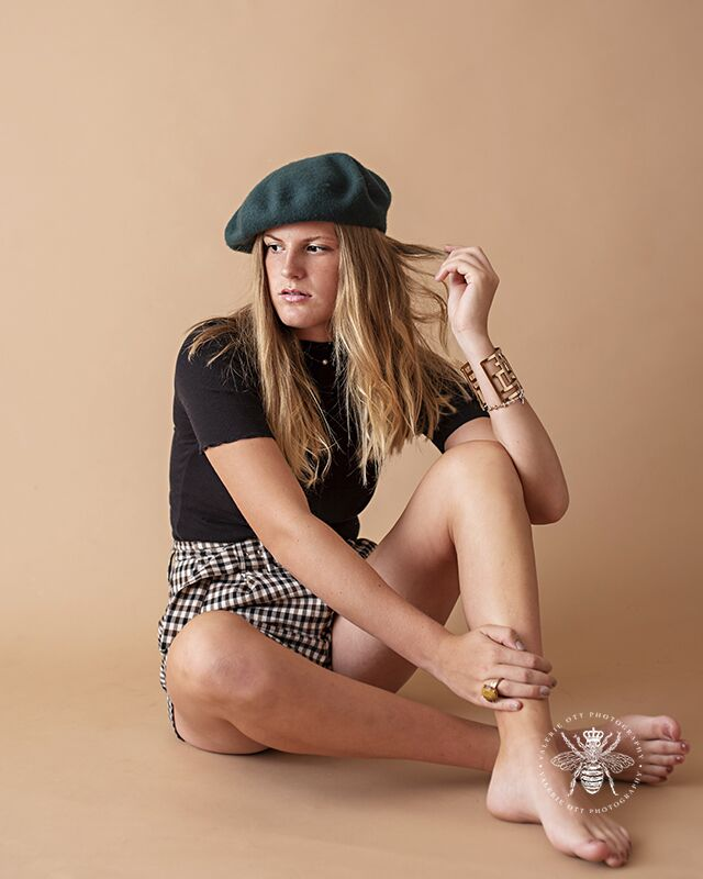 Model poses sitting and running her fingers through her hair for modeling headshots in a studio. She wears gingham shorts, a black top, and a dark green beret.