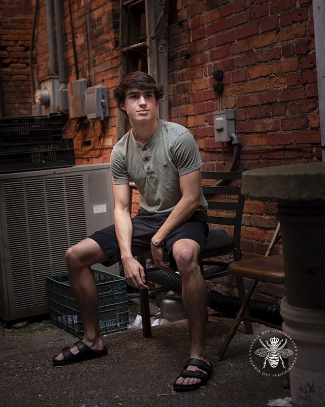 Portage Northern senior guy poses sitting in an alley in Downtown Kalamazoo. He wears black shorts, a gray t shirt, and sandals.