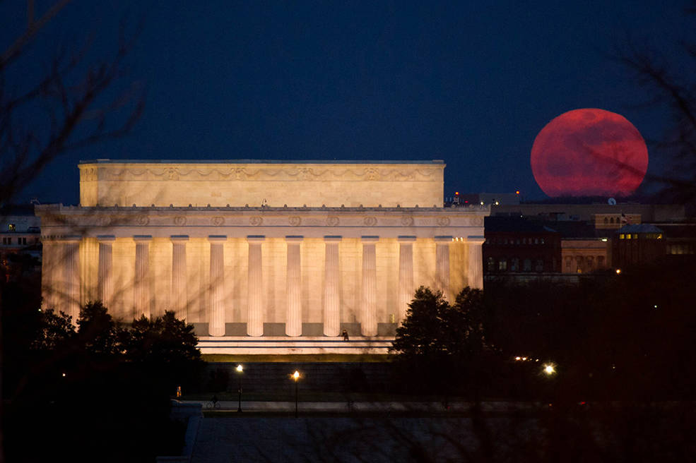 """The full moon is seen as it rises near the Lincoln Memorial, Saturday, March 19, 2011, in Washington. The full moon tonight is called a """"Super Perigee Moon"""" since it is at it's closest to Earth in 2011. The last full moon so big and close to Earth occurred in March of 1993. Photo Credit: (NASA/Bill Ingalls)"""