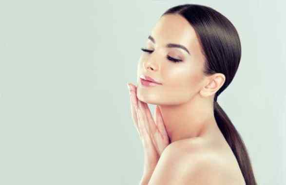 Image of a Gorgeous, young woman is demonstrating clean fresh skin and touching own face.