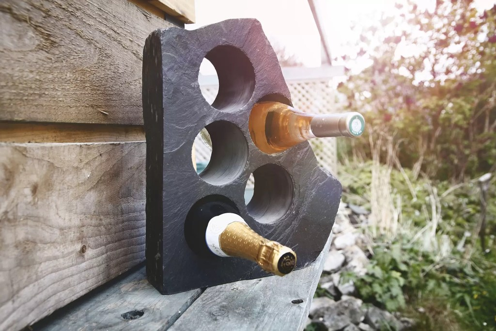 Blue grey Welsh slate wine rack with two bottles of wine glistening in the sunshine