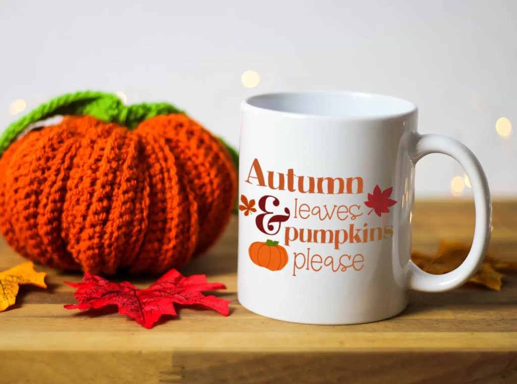 Ceramic white mug with an illustration of a pumpkin and the words autumn leaves and pumpkins please