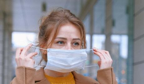Woman putting mask on