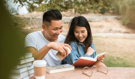 Couple reading a book outdoors