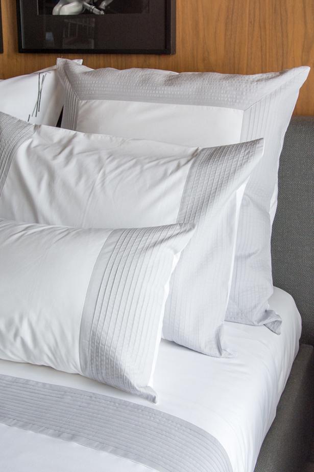 quarto com roupa de cama branca e cinza valencien
