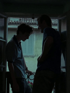 Elio and Oliver's silhouettes. They stand in front of each other, framed by an open window.