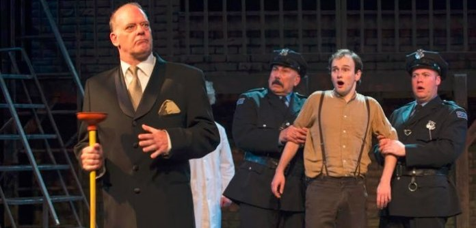 Andrew Wheeler as Caldwell B. Caldwell and members of the cast of Urinetown The Musical