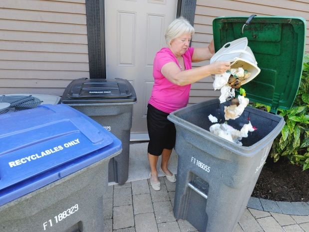 Janice Zeilstra dumps organic waste into a bin provided by the City of Surrey at her home.