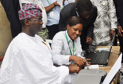 An INEC official Mrs. Seye Soriyan, HOU ICT, INEC Lagos, Assisting Governor Babatunde Fashola, at Word G,3, Idita zone, Itolo Street, Surulere, during the on-going Voters Registration Exercise in Lagos. Photo by Bunmi Azeez