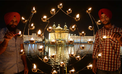 NDIA, Amritsar : Indian Sikh devotees lights candles at the illuminated Sikhism's holiest shrine Golden Temple in Amritsar on November 3, 2013, on the ocassion of Bandi Chhor Divas or Diwali. Sikhs celebrate Bandi Chhor Divas or Diwali to mark the return of the Sixth Guru, Guru Hargobind Ji, who was freed from imprisonment and also managed to release 52 political prisoners at the same time from Gwalior fort by Mughal Emperor Jahangir in 1619. AFP PHOTO