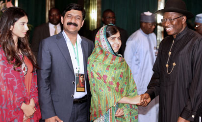 Pakistani education activist Malala Yousafzai (L) watches on July 14, 2014 Nigerian President Goodluck Jonathan look at a book at the State House in Abuja. Malala on July 14 urged Jonathan to meet with parents of the schoolgirls kidnapped three months ago by Boko Haram. Malala, who survived a Taliban assassination attempt in 2012 and has become a champion for access to schooling, was in Abuja on her 17th birthday to mark the somber anniversary of Boko Haram's April 14 abduction of 276 girls from a secondary school in the northeast Nigerian city of Chibok.  AFP PHOTO