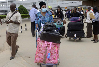 EBOLA ALERT  AT MMIA—A woman, wears protective face masks and hand gloves upon arrival at the Murtala Mohammed Airport, Lagos , yesterday. Inset: Security personnel with masks on duty at the airport. Photos: AFP.
