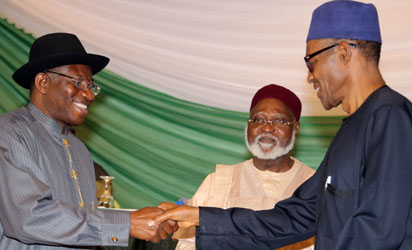Nigerian President Goodluck Jonathan (L), and APC main opposition party's presidential candidate Mohammadu Buhari shake hands under the eyes of Chairman of the Abuja Peace Accord former Head of State General Abdulsalami Abubakar (C), after signing the renewal of the pledges for peaceful elections on March 26, 2015 in Abuja. Security is a major concern at Saturday's vote both from Boko Haram violence against voters and polling stations to clashes between rival supporters. In 2011, around 1,000 people were killed in violence after Jonathan beat Buhari to the presidency. AFP PHOTO