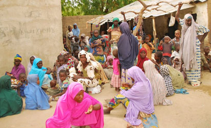 This handout picture released by the Nigerian army on April 30, 2015 and taken this week in an undisclosed location in the Sambisa Forest, Borno state, purportedly shows a member of the Nigerian Army standing next to a group of women and children rescued in an operation against the Islamist group Boko Haram. Boko Haram hostages were held in atrocious conditions in the group's Sambisa Forest stronghold, Nigeria's military said on April 30 after nearly 500 women and girls were released this week. AFP PHOTO / NIGERIAN ARMY