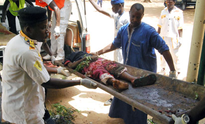 Health officials carry the body of a victim  of a suicide bomb attack out of an ambulance in  Potiskum, in northeast Nigeria's Yobe State, on June 15, 2015. Ten people were killed in twin suicide bombings in Potiskum, northeast Nigeria, a police source and a civilian vigilante assisting the military against Boko Haram told AFP on June 15. Eight vigilantes were killed in the first blast in the Igwanda area of the city, while two died in the second outside a tavern and brothel in the Dorawa area. AFP PHOTO