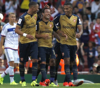 """Arsenal's Spanish midfielder Santi Cazorla (C) celebrates after scoring during the pre-season friendly football match between Arsenal and Lyon at The Emirates Stadium in north London on July 25, 2015, the game is one of four matches played over two days for the Emirates Cup. AFP PHOTO / IAN KINGTON RESTRICTED TO EDITORIAL USE. No use with unauthorised audio, video, data, fixture lists, club/league logos or """"live"""" services. Online in-match use limited to 45 images, no video emulation. No use in betting, games or single club/league/player publications."""