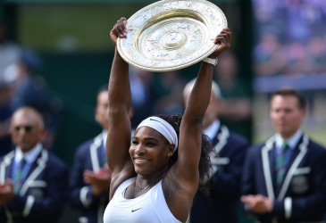 US player Serena Williams celebrates with the winner's trophy, the Venus Rosewater Dish, after her women's singles final victory over Spain's Garbine Muguruza on day twelve of the 2015 Wimbledon Championships at The All England Tennis Club in Wimbledon, southwest London, on July 11, 2015.   RESTRICTED TO EDITORIAL USE  --  AFP PHOTO / GLYN KIRK