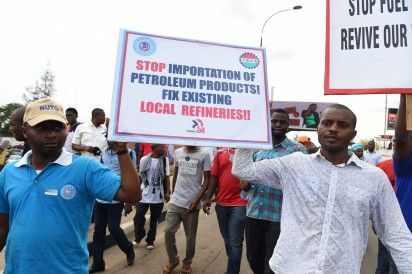 """Workers carry placards during a protest demanding that the government reinstate prices of fuel at 86.50 naira ($0.43, 0.38 euros) per litre in Lagos, on May 18, 2016. Nigeria's government on May 18 warned against """"illegal strike action"""" after some union members vowed to press ahead with a national strike over petrol price rises despite a court injunction.    / AFP PHOTO"""