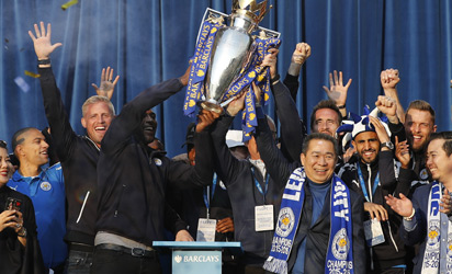 Leicester City's English captain and defender Wes Morgan (C left) and Leicester City's Thai owner and chairman Vichai Srivaddhanaprabha (C right) hold aloft the Premier league trophy as the Leicester City football team celebrate in front of fans in Victoria Park, after taking part in an open-top bus parade through Leicester, to celebrate winning the Premier League title on May 16, 2016. / AFP PHOTO