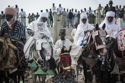 A boy sits on his horse waiting to see the Emir of Kano's procession passing during the Durbar procession in Kano,on July 6, 2016. Kano celebrates Eid al-Fitr with the Durbar festival, an event that sees a parade of the Emir and his entourage go through the streets of the city on horseback accompanied by musicians.