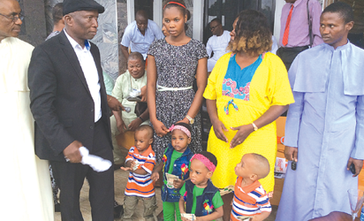 The children with their mother and their benefactor, Chief Louis Onwugbenu (in suit)