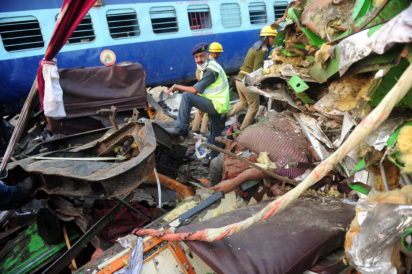 EDITORS NOTE: Graphic content / Indian rescue personnel stand near a body in the wreckage of a train that derailed near Pukhrayan in Kanpur district on November 20, 2016. Emergency workers raced November 20 to find any more survivors in the mangled wreckage of an Indian train that derailed overnight, killing at least 116 people, in the worst disaster to hit the country's ageing rail network in recent years. / AFP PHOTO / SANJAY KANOJIA