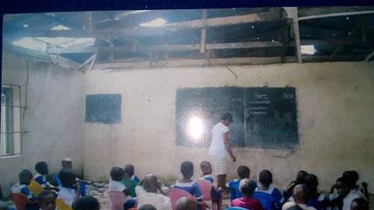 Teacher, pupils in a dilapidated   classroom