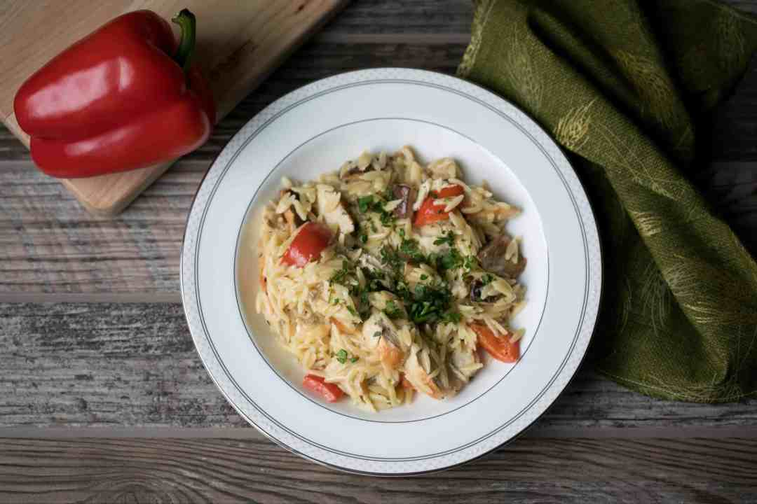 bowl of creamy orzo pasta with chicken and red peppers