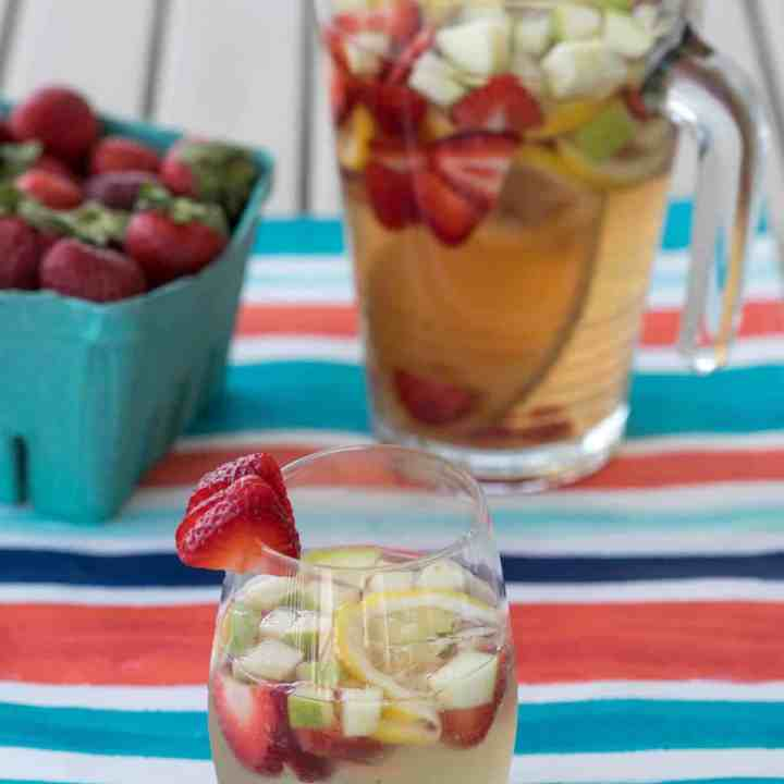 white wine sangria in a cup and a pitcher with strawberries, green apple, and lemon