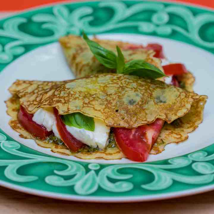 side view of crepe filled with tomatoes, pesto, and mozzarella cheese with 2nd crepe behind it