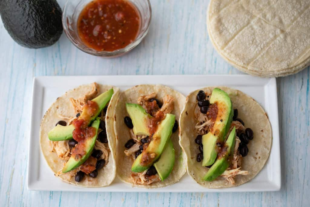 slow cooker chicken tacos with avocado, salsa, black beans, and corn tortillas