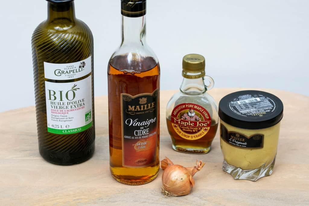 ingredients for apple cider vinegar salad dressing: olive oil, cider vinegar, maple syrup, dijon mustard, and shallot