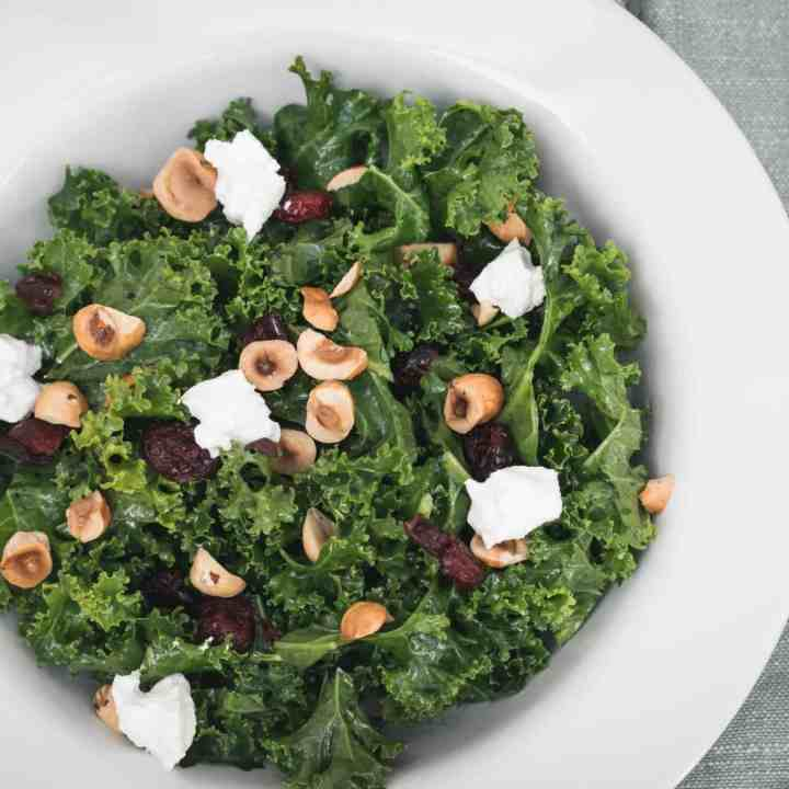closeup of kale salad with cranberries, goat cheese, and hazelnuts