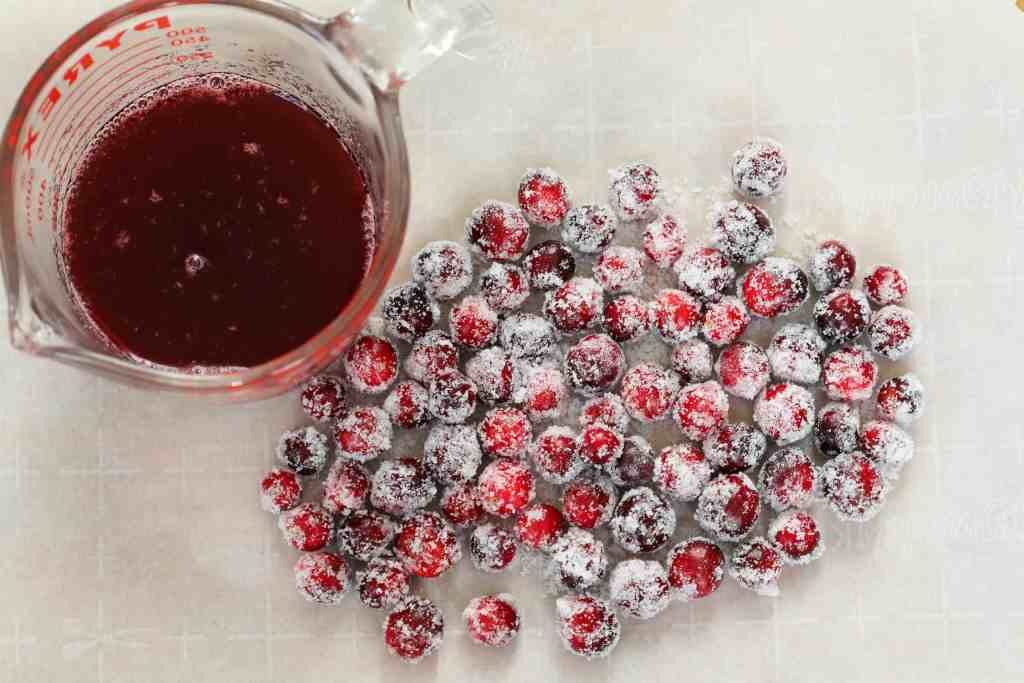 cranberry syrup next to sugared cranberries on parchment paper