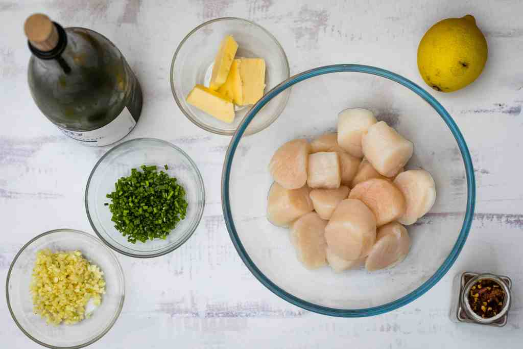 ingredients for spicy scallop scampi: white wine, garlic, chives, butter, scallops, lemon, red pepper