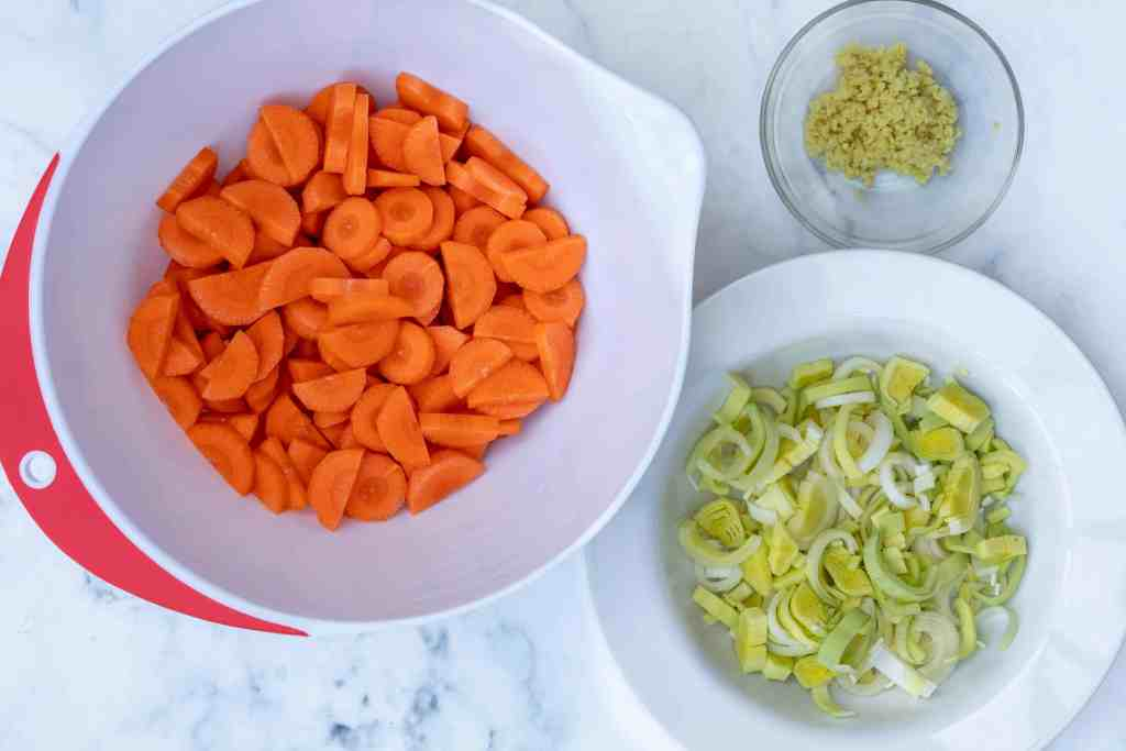 prepped ingredients for carrot ginger soup: carrots, leeks, ginger