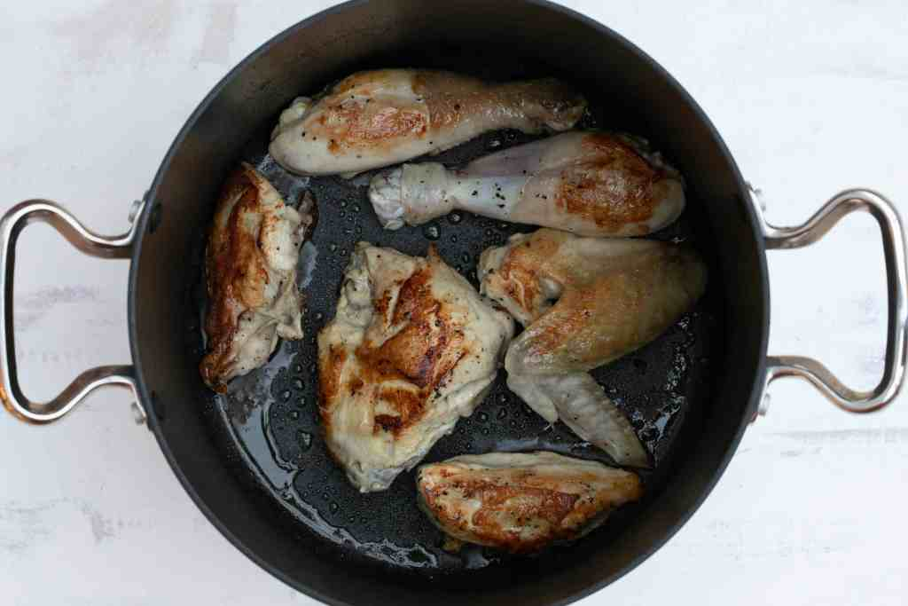 chicken pieces browned in saucepan