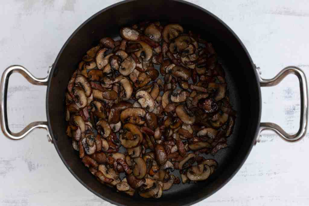 mushrooms and bacon browned in saucepan for coq au vin blanc